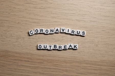 the word CORONAVIRUS OUTBREAK in white cubes on a light wooden background. Coronavirus design template.