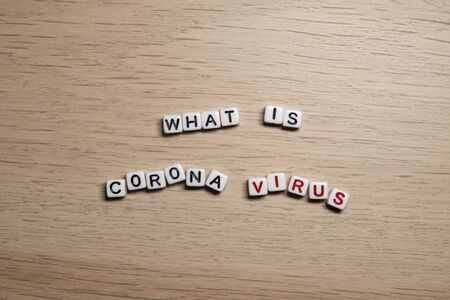 the word WHAT IS CORONA VIRUS in white cubes on a light wooden background. CoronaVirus design template. Imagens