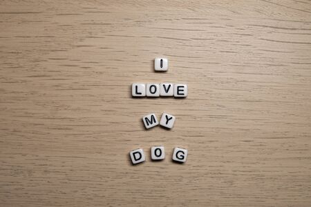 Word I LOVE MY DOG in white cubes on light wooden background for your design templates.