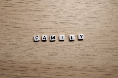 Word FAMILY in white cubes on light wooden background for your design templates.
