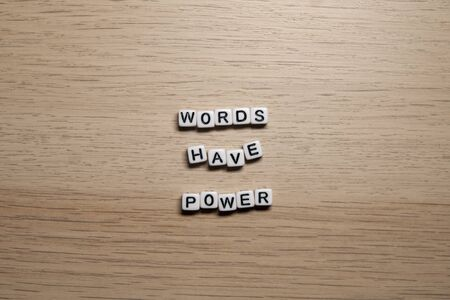 Word WORDS HAVE POWER in white cubes on light wooden background for your design templates.