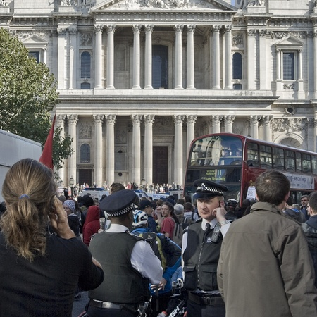 occupy london: London, England - October 15 2011 - Police stand in the crowd overlooking the first day of the Occupy London protests