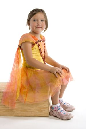 highkey: Young grade school aged girl sitting on a wooden box isolated against a white background Stock Photo