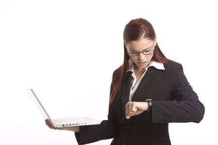 Woman worker checking her watch as she holds a laptop computer Stock Photo