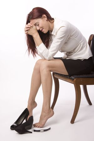 Woman in skirt and blouse sitting on chair crying after bad day