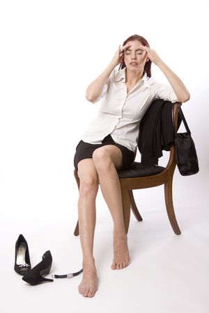 wasted: Woman in business attire sitting on a chair and holding her head Stock Photo