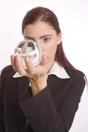 foreshadow: Pretty young woman in business attire looking at crystal ball