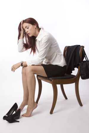 weary: Woman in blouse and skirt sitting on chair at end of the day looking world weary
