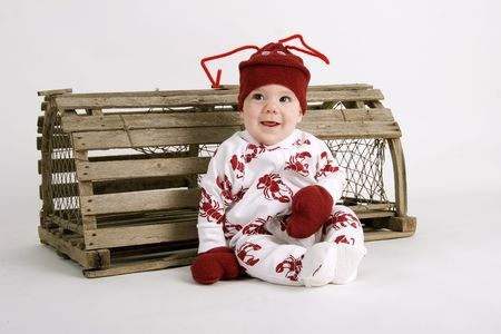 Baby dressed in lobster costume sitting next to a lobster trap Reklamní fotografie