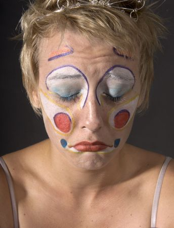 Closeup of a woman clown with a sad look on her face