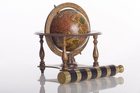 Old world globe and spyglass isolated against white Imagens