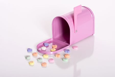 wooing: Pink mailbox surrounded by valentine candy hearts isolated against a white background.
