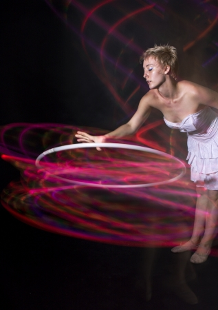 Young woman hula hooping against black background