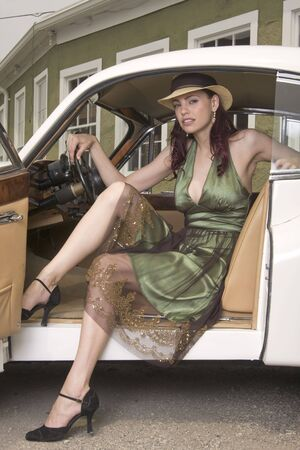 Beautiful woman in summer hat and dress stepping out of a vintage sports car.