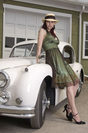 Beautiful woman leaning on a classic car