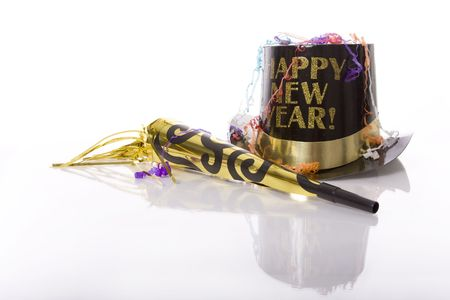 Party favors including top hat that says Happy New Year  and horn isolated against white background