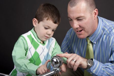 Father and young son looking at a bell on the handlebars of a tricycle