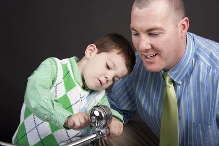 Father and son inspecting the bell on a tricycle Stock Photo - 5824300