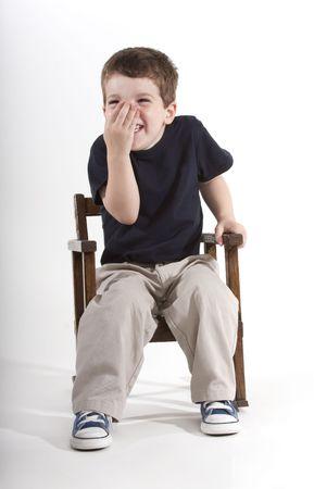 chłopięctwo: MÅ'ode przedszkolnym wiek ChÅ'opiec siedzi w KrzesÅ'o obrotowe giggling rÄ™kÄ… nad jego twarzy