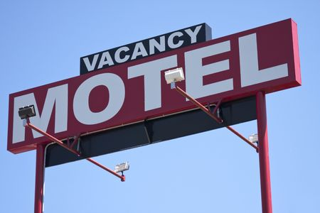 Red motel roadside sign with vacancy on top of it