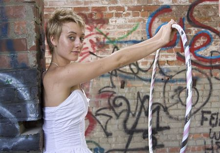 Young woman with closely cropped hair standing in front of graffeti covered wall