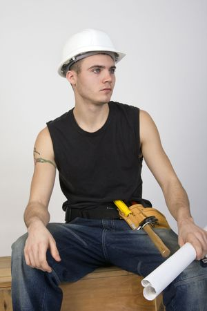 Young man wearing hardhat and toolbelt, sitting on a wooden crate and holding a set of blueprints.