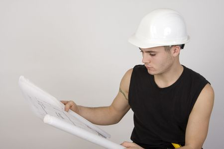 Young man in hardhat looking over a set of blueprints