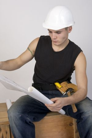 Young man in hard hat and toolbelt studying a set of blueprints. Reklamní fotografie