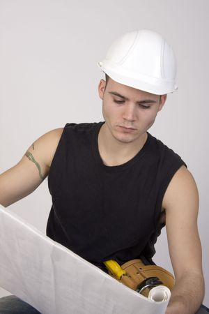 Young man wearing hardhat and toolbelt studying set of blueprints. Reklamní fotografie