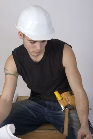 Young man in a hardhat land toolbelt ooking at blueprints Reklamní fotografie