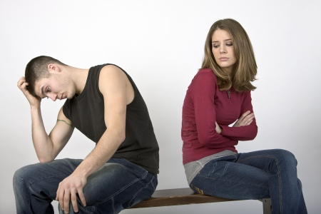 spat: Young couple sitting on a bench seemingly in a spat.