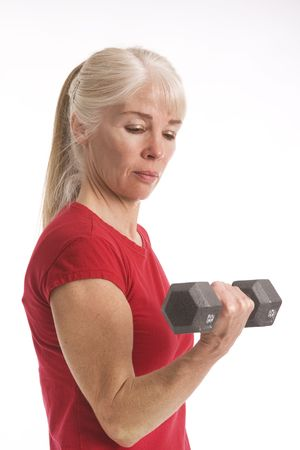 Middle-aged woman working out with barbell isolated against white background
