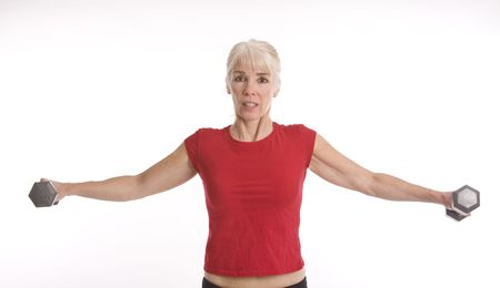 Middle-aged woman working out with weights against white background Reklamní fotografie