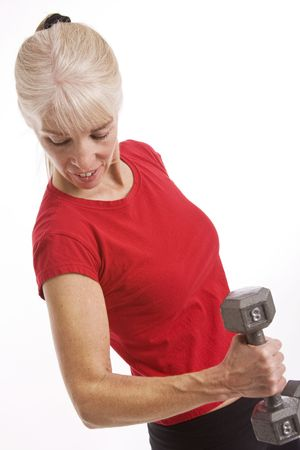 Middle-aged woman working out with weights isolated against white background