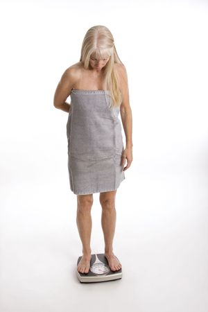Middle-aged woman wrapped in towel standing on scale isolated against white background