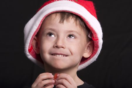 Young boy wearing Santa Claus hat, holding piece of candy, posed against black background