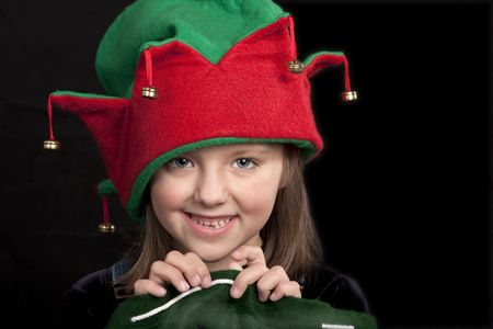 Portrait of young girl dressed in red and green Christmas hat.