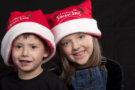 Young boy and girl wearing Santa Claus hats posed against a black background Reklamní fotografie