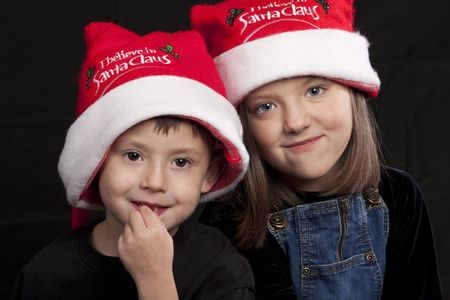 Young boy and girl dressed in red Santa Claus hats Reklamní fotografie