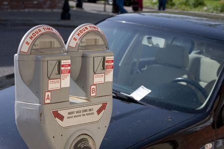 parked: Parkeer meter met een auto op de achtergrond met een ticket op de voorruit  Stockfoto