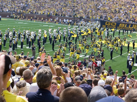 University of Michigan football players run onto the field at the Big House in Ann Arbor, Michigan, during the 2011 season opener against Western Michigan University of Saturday, Sept. 3, 2011.