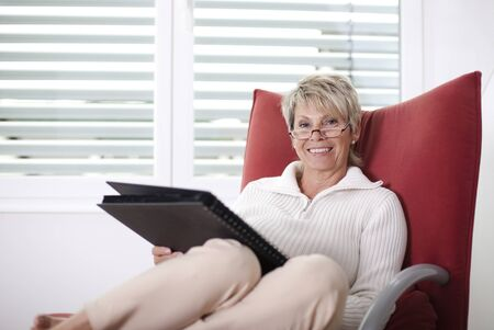 older woman holds on chair a photo album photo