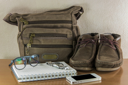 Still life with casual man, boots and bag on wooden table over grunge background. photo