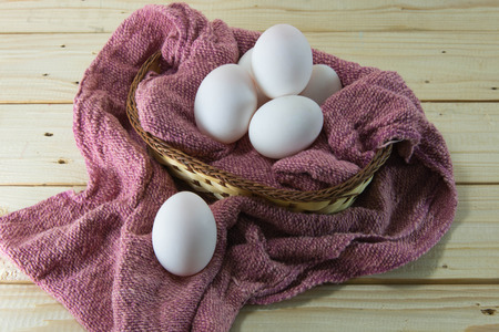 all in one: Fresh eggs in a woven basket with red dish towel. Selective focus on eggs with shallow dof. Concept - all eggs in one basket