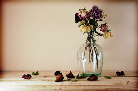 Still life with flowers on wooden table over grunge background, vintage style selective focus on dry flower in a vase photo