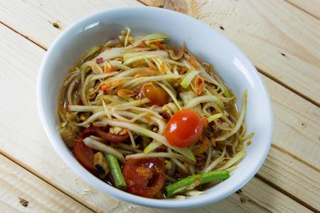 goi: Green papaya salad thai food style on wood background