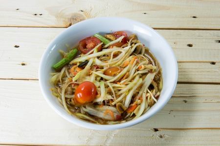goi: Green papaya salad thai food style on wood background