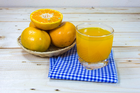 Glass of delicious orange juice and slices of orange on wooden table background photo