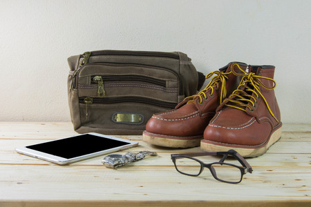 Still life with casual man, boots and bag on wooden table background photo