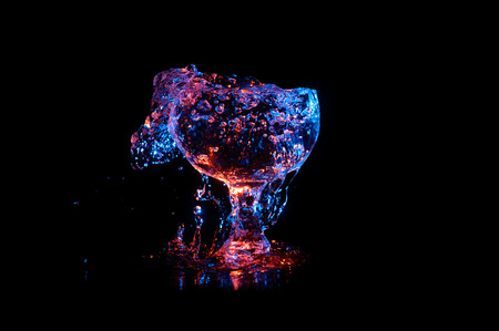 Glass Chalice overflowing with clear liquid under colored lights on a black background Stock Photo